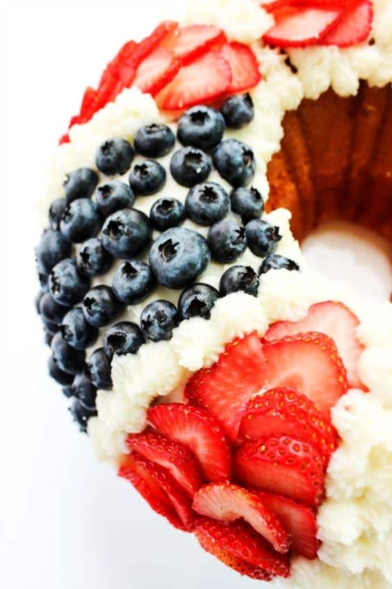 The Red White and Blue Bundt Cake has distinct strips of cut strawberries, blueberries, and pipped vanilla frosting.