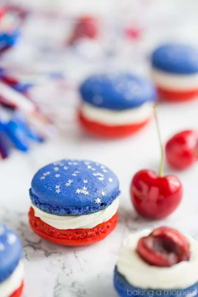The Red, White, and Blue Cherry Cheesecake Macarons has a white frosting, and one cookie is red and the other blue with star sprinkles.