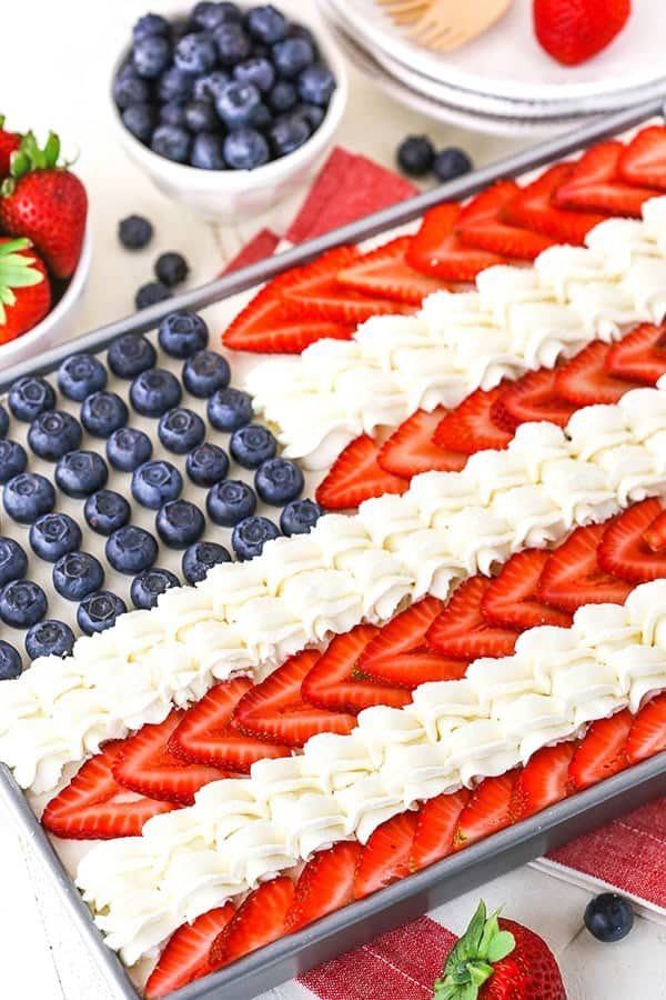 On a baking sheet, the Angel Food Flag Cake has blueberries in the blue section of the flag, and strawberries and white frosting makes up the stripes.