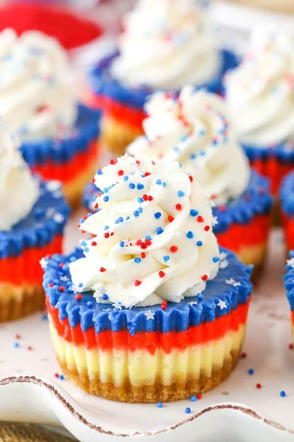 The Red, White, and Blue Mini Cheesecakes has distinct layer of a graham cracker crust, white, red, and blue cheesecake and topped with whipped cream and sprinkles.