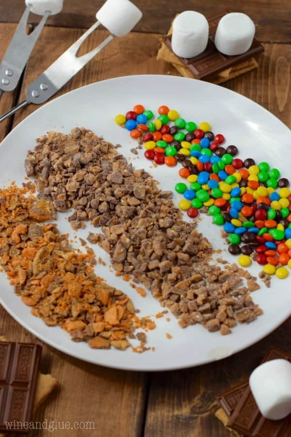 On a white plate, there are distinct rows of the Candy Coated S'more's coating (broken pieces of Butterfingers, M&Ms, and toffee)