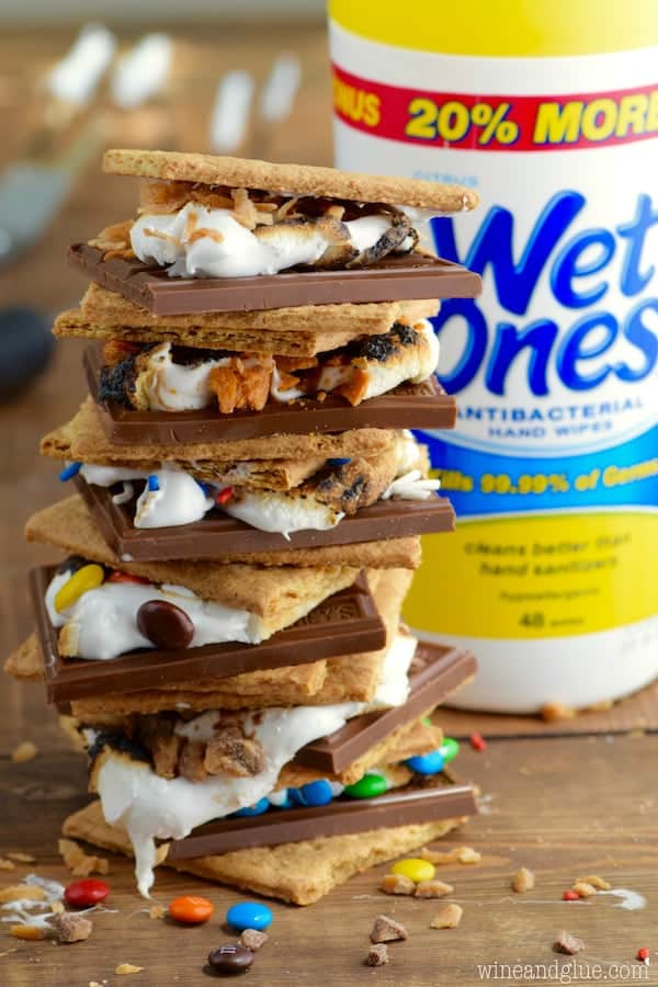 In front of Wet Ones, the Candy Coated S'mores is stacked on top of each other showing the cut chocolate bar, M&Ms, sprinkles, Butterfinger, melted marshmallow, and graham crackers.