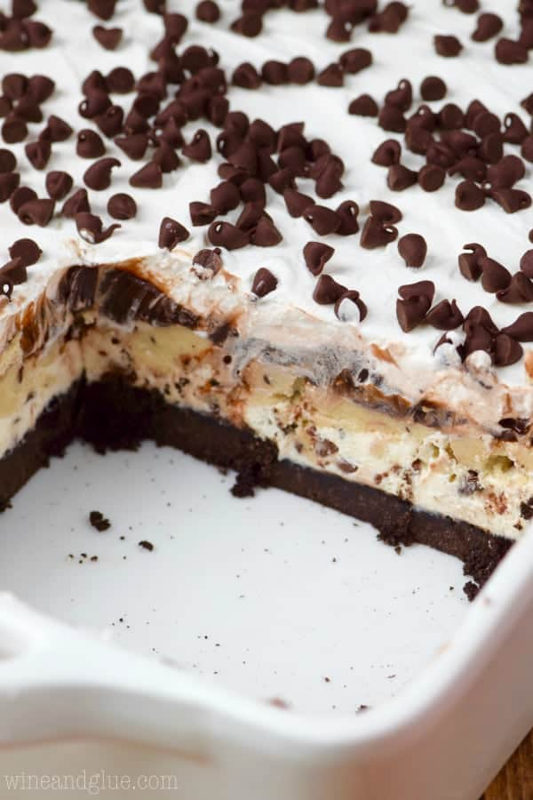 In a ceramic casserole dish, the Cookie Dough Lush has a little rectangular slice cut our showing the distinct layers of the Oreo crust, cookie dough filling, and a white fluffy frosting with mini chocolate chips.