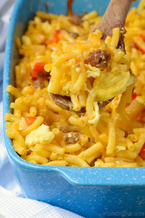 In a blue casserole dish, the Mac N' Cheese Breakfast Casserole has chunks of sausage, Mac and Cheese, eggs, and sliced red peppers.