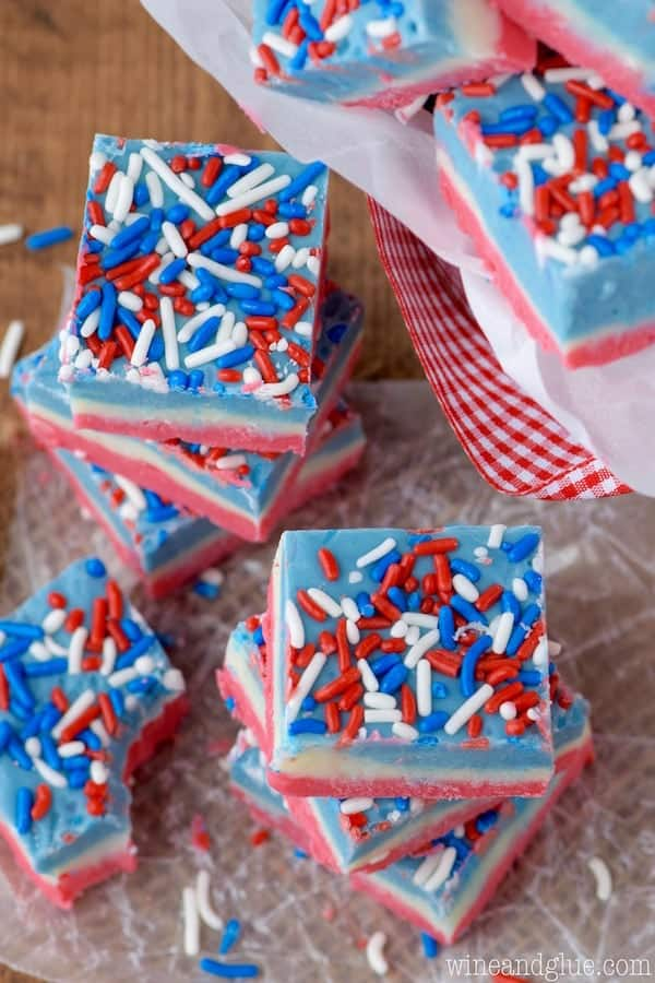 The Red, White, and Blue Fudge are stacked on top of each other and has the distinct colored layers and topped with red, white, and blue sprinkles.