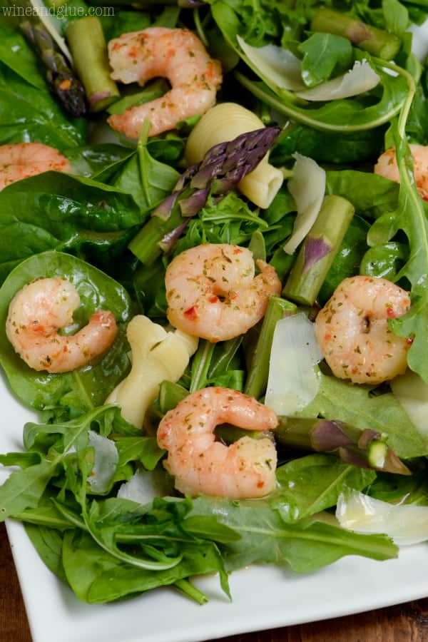 A closeup photo of the Shrimp Scampi Salad showing the seasoned shrimp, chopped asparagus, arugula, parmesan, noodles, and spinach.