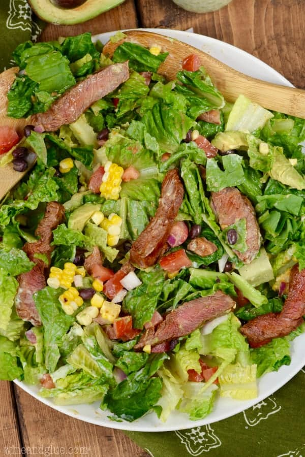 The Southwestern Steak Salad is mixed together with romaine lettuce, corn, black bean, tomatoes, avocado, and sliced steak.