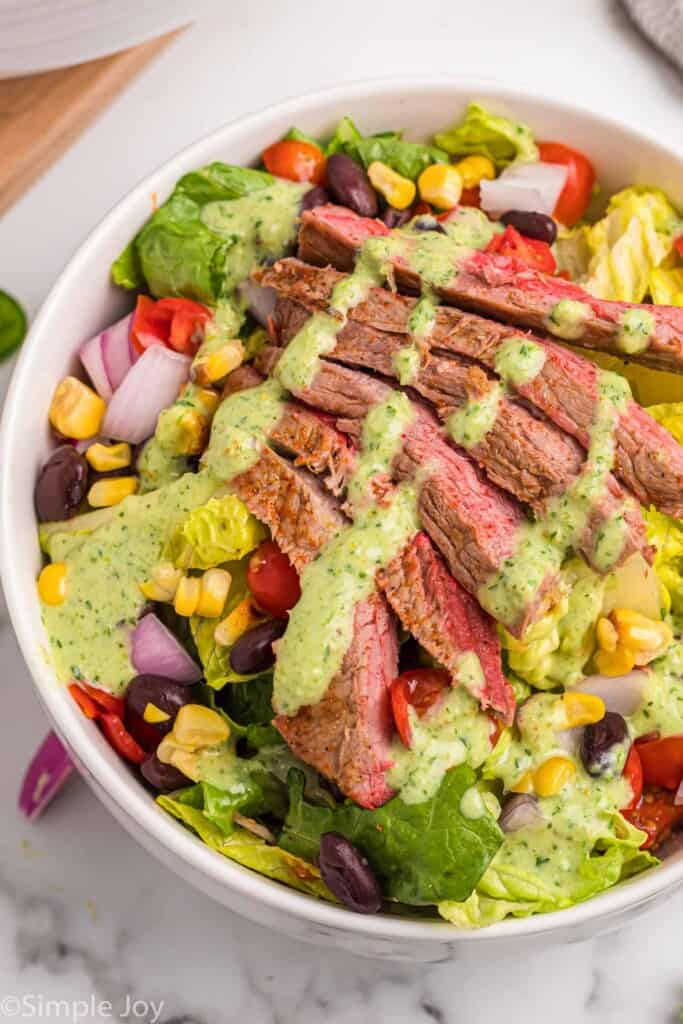 close up of a steak salad in a white bowl with dressing drizzled over the top