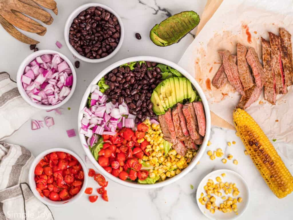 overhead photo of ingredients for a steak salad in a bowl with more ingredients around the bowl