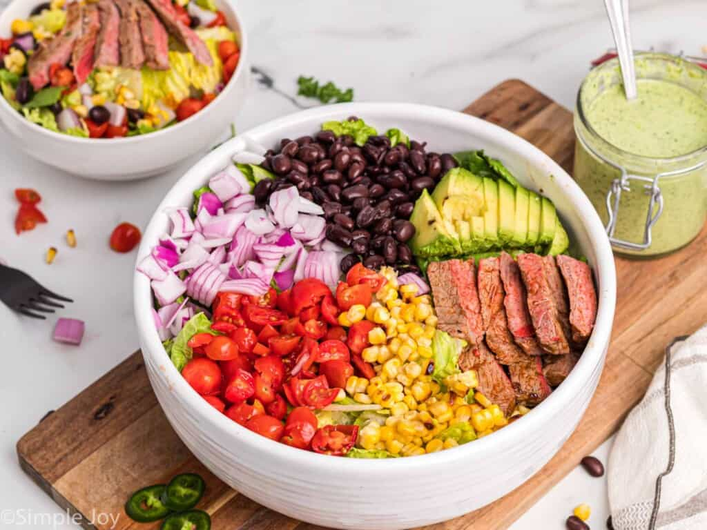 side view of a salad with steak in a big white bowl with dressing next to it