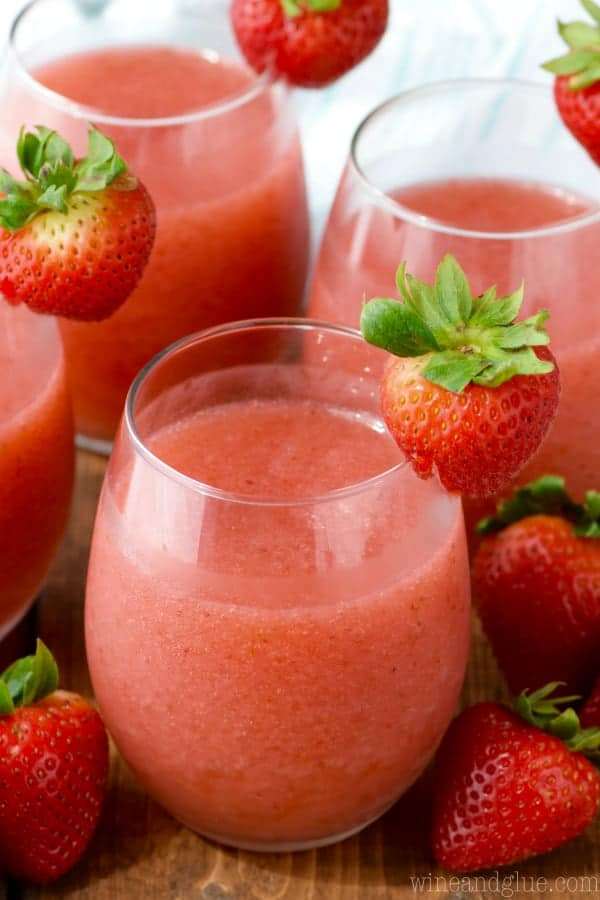 In glasses, the Strawberry Daiquiri Sangria have a frosted red coloring and on the rim is a strawberry.
