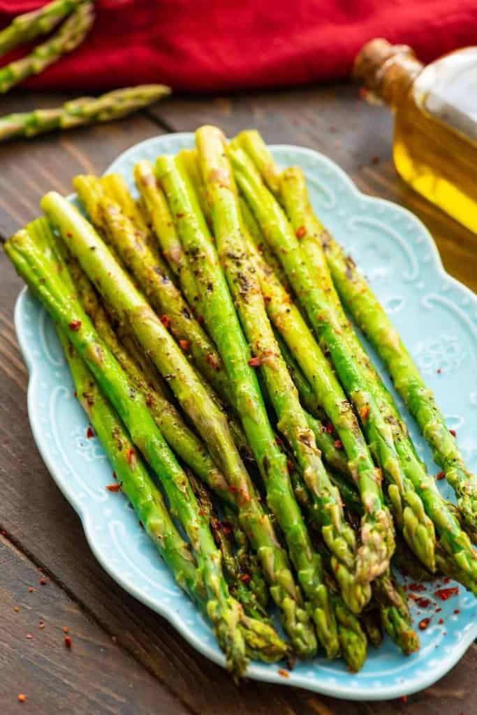 The Grilled Asparagus are on a blue platter topped with pepper.