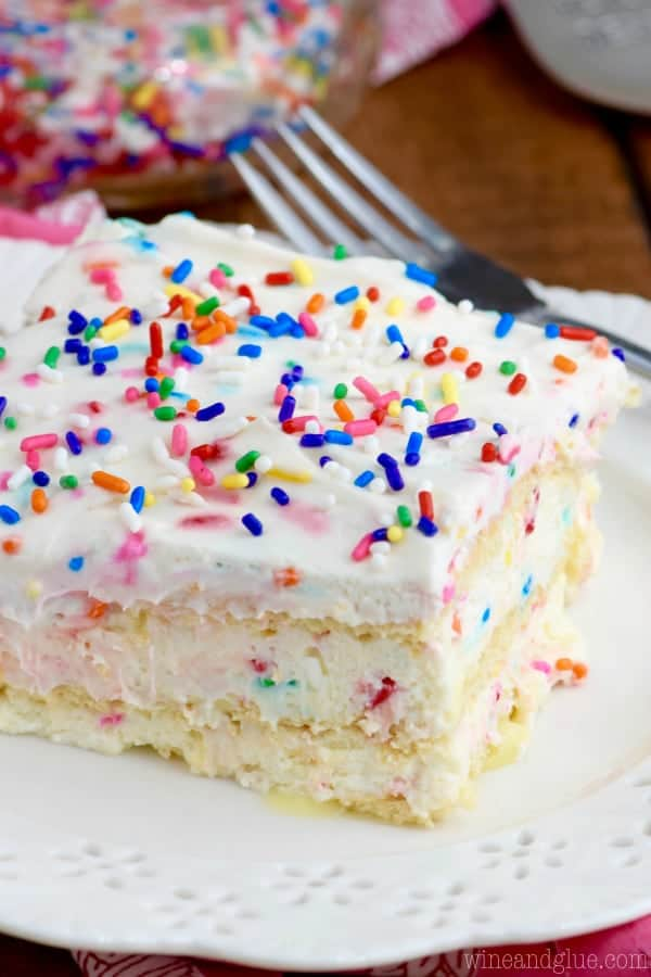 The No Bake Birthday Cake Lasagna has a pudding like texture middle speckled in between crackers with colors and on top with frosting and rainbow sprinkles.