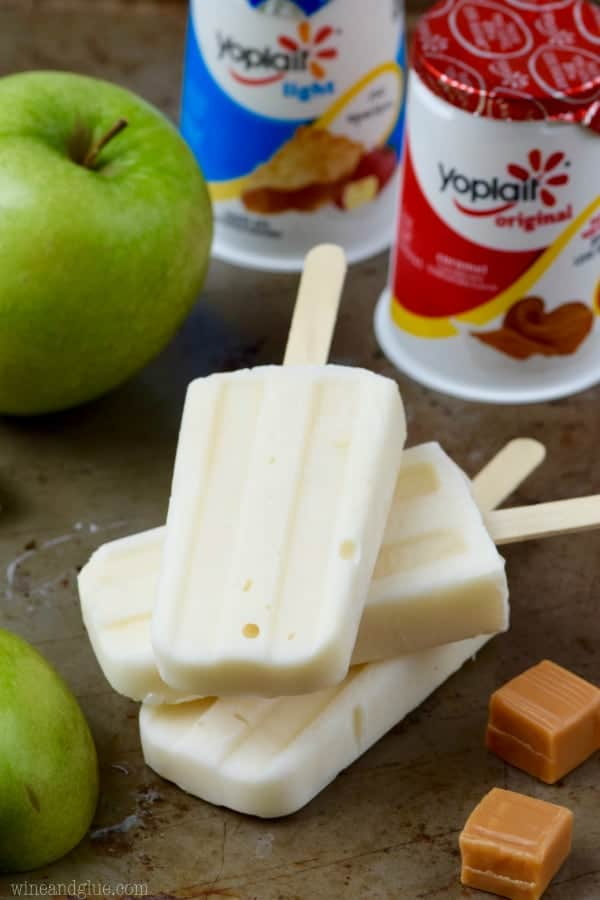 Three of the Lighter Caramel Apple Pipe Pops are stacked on top of each other and in front of the Yoplait yogurt.