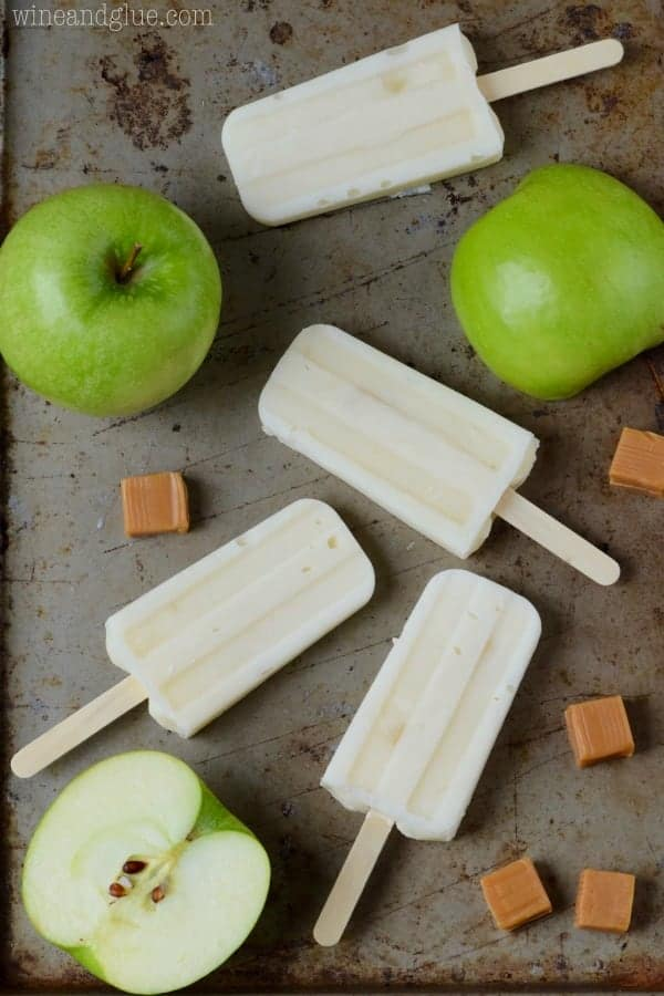 On a baking sheet, the Lighter Caramel Apple Pipe Pops are surrounded by Green apples and caramel cubes.