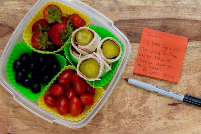 A lunch box filled with strawberries, Salami Pickles Roll, cherry tomatoes, and olives next to a lunch note.