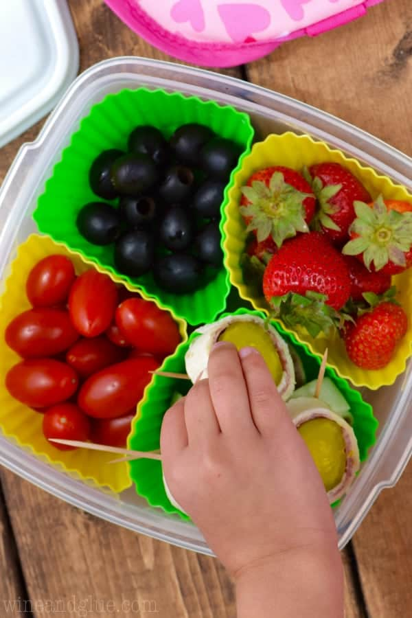 A child is grabbing one of the Salami Pickle Rolls which is in a lunch box with olives, cherry tomatoes, and strawberries.