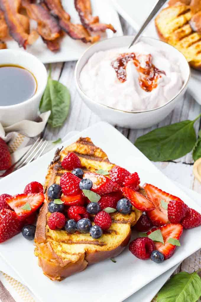 The Grilled French Toast has grilled marks on it and topped with raspberries, blueberries, and strawberries.