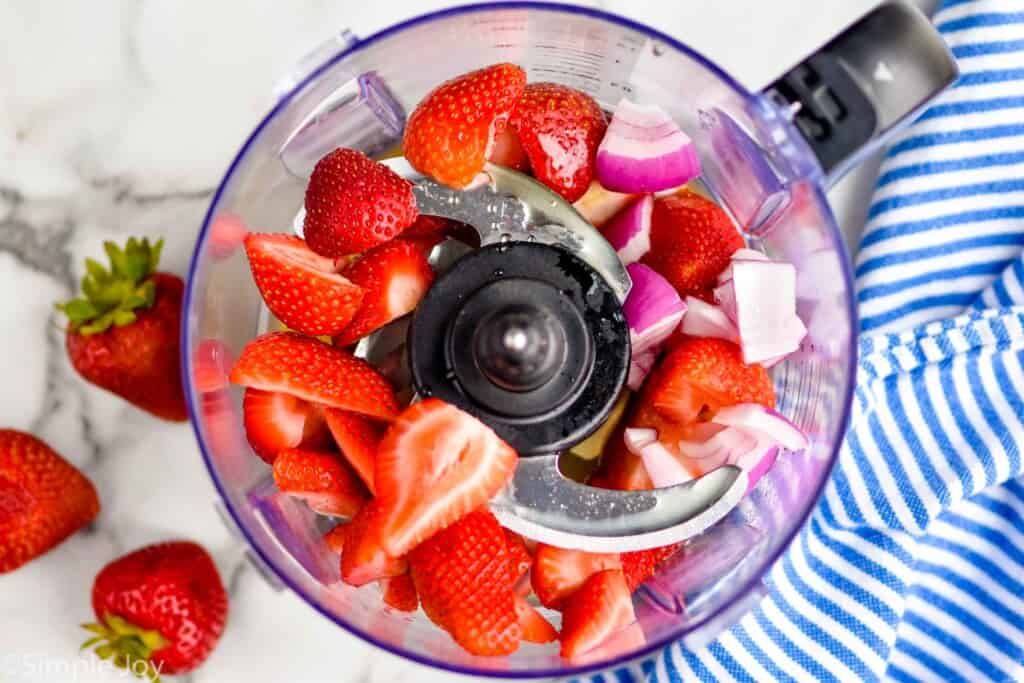halved strawberries and other ingredients in a food processor to make salad dressing