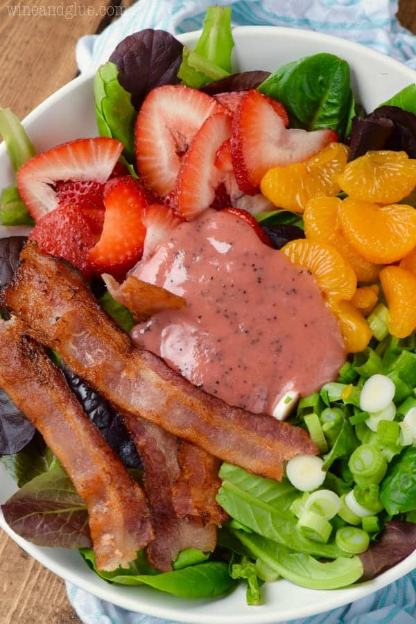 The Strawberry Bacon Salad has strips of bacon, clementines, cut strawberries, chives, and mixed greens topped with a strawberry dressing.
