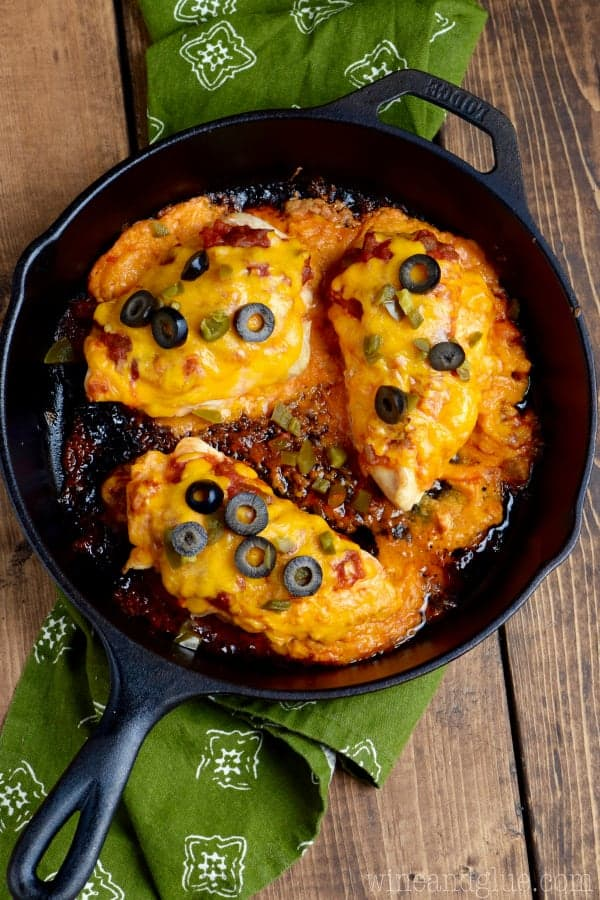 In a cast iron skillet, three Stuffed Taco Chickens are fully cooked with melted cheddar cheese, black olives, and minced jalapenos.