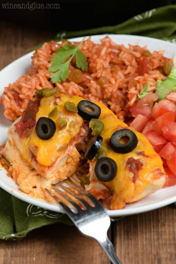 On a white plate, the Stuffed Taco Chicken is covered with melted cheese, olives, and minced jalapenos with sides of cut tomatoes, lettuce, and rice.