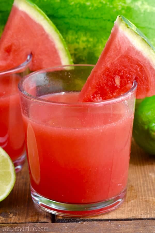 In a glass cup, the Watermelon Limeade has red/pink color and a slice of watermelon on the rim.