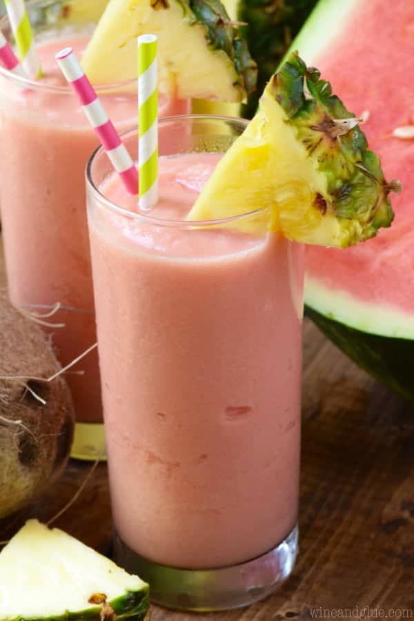 The Watermelon Pina Colada has a pink tint and a slice of pineapple on the rim.