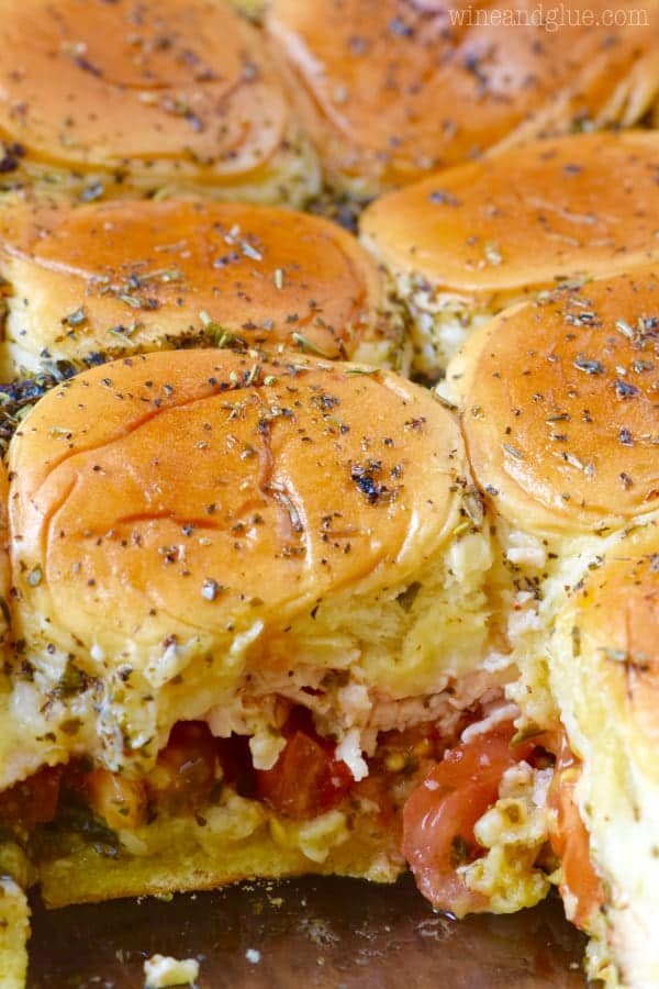 A closeup photo of the Italian Peso Sliders in the casserole dish and one is taken out showing the distinct layers of pesto, tomatoes, turkey, and cheese.