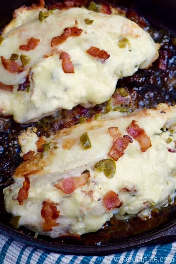 A cast iron skillet has two Jalapeno Popper Stuffed Chicken is covered with melted cheese and topped with bacon and jalapeno slices.
