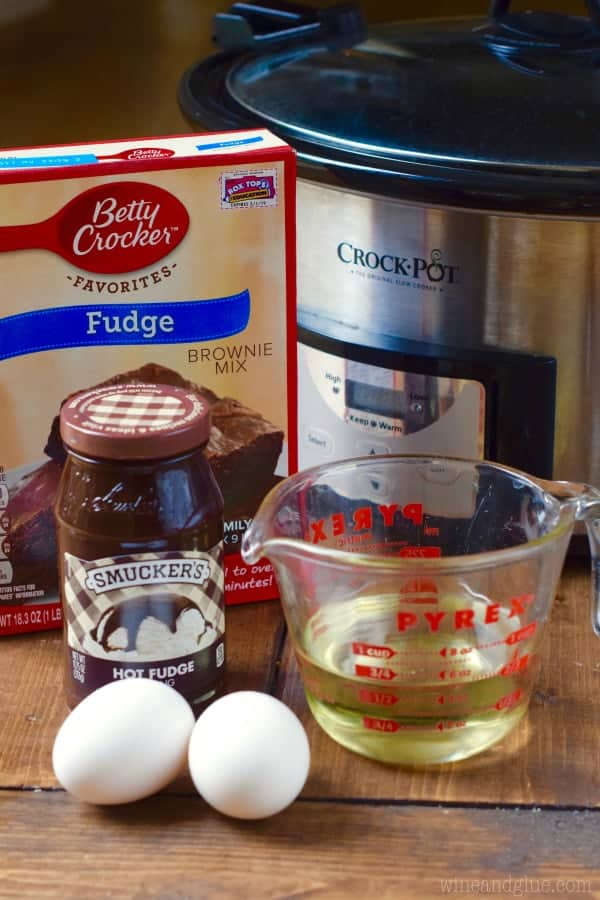 In front of the Crock Pot, the ingredients for the Slow Cooker Hot Fudge Brownies are two eggs, Smucker's Hot Fudge, Betty Crocker's Fudge, two eggs, and oil.