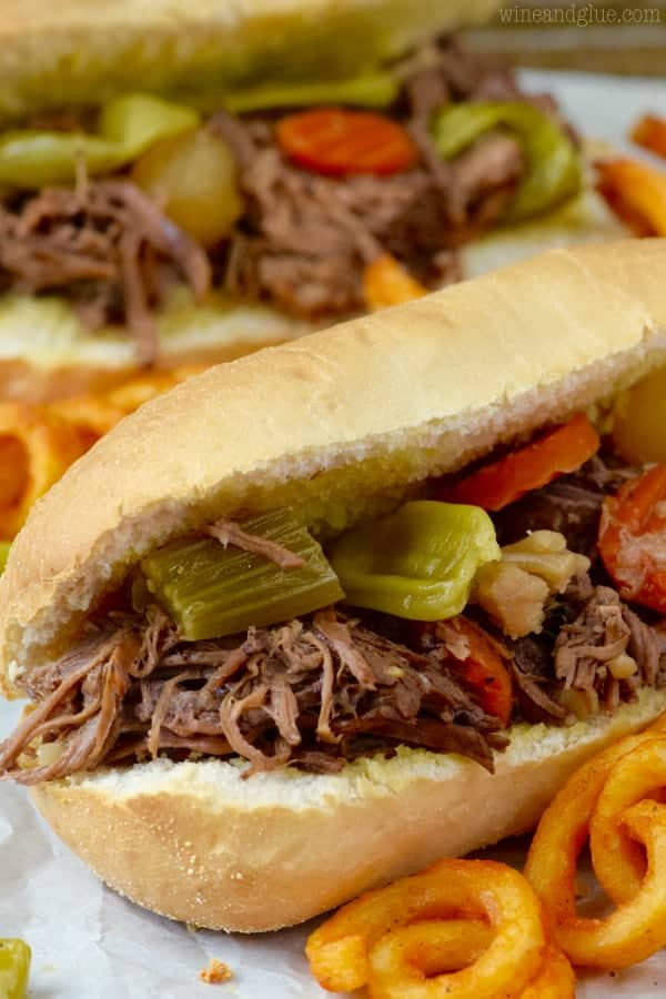 up close of an italian beef sandwich with gardenia mix on a roll next to curly fries