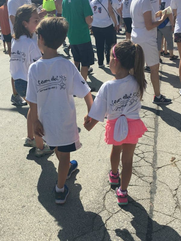 Two children holding hands wearing Team Elliot t-shirts.