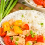 pinterest graphic showing a shallow bowl holding sweet and sour chicken and rice, garnished with scallions