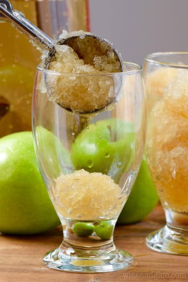 An ice cream scoopers scoops in some of the Apple Brandy Slush into glasses.