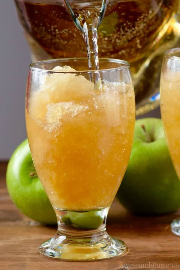 Some of the Apple Brandy Slush in the glass, and some of the ginger ale being poured into it.