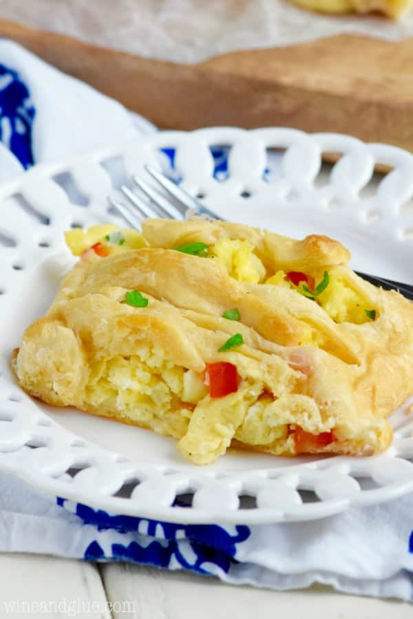 On a white plate, a slice of the Breakfast Braid shows the fluffy eggs with diced red peppers in the middle.
