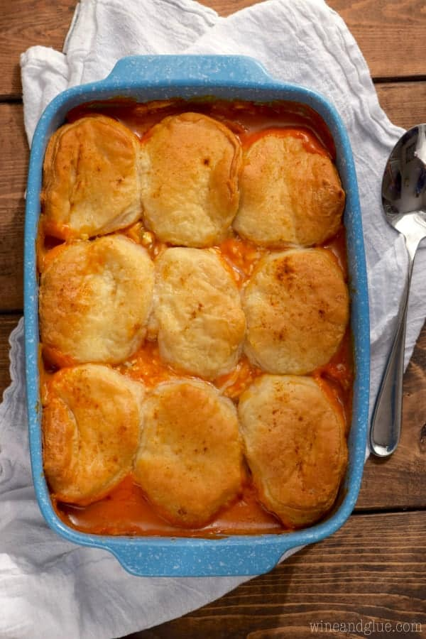 In a blue casserole dish, the Buffalo Chicken Pot Pie has a bright red filling from the buffalo sauce and covered by golden brown biscuits.