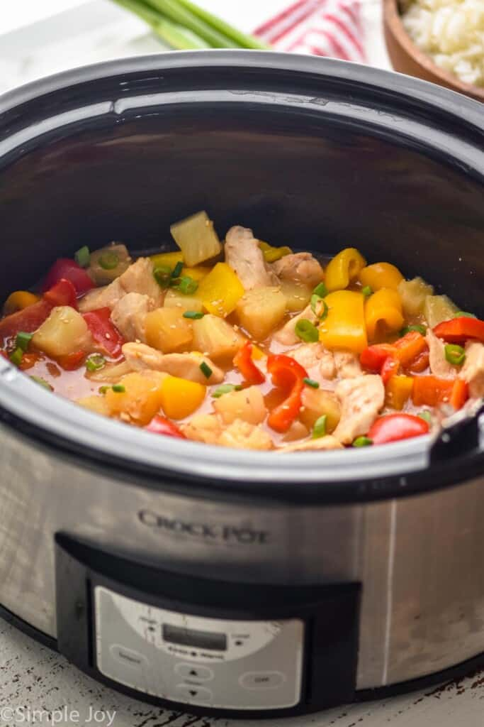 side view of crockpot sweet and sour chicken in a slow cooker