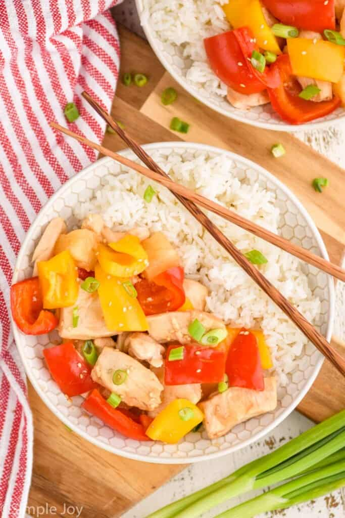 overhead view of a bowl of slow cooker sweet and sour chicken with rice, chopsticks laying over the top