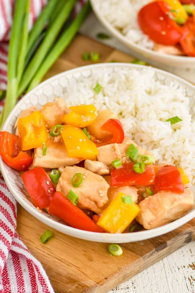 showing a shallow bowl holding sweet and sour chicken and rice, garnished with scallions