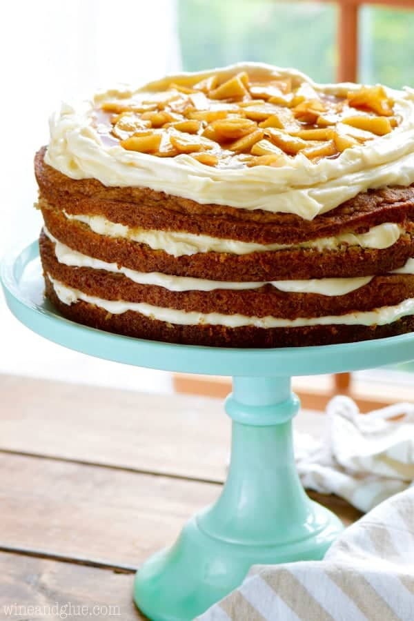On a blue cake stand, the Naked Apple Spice Cake has raw edges and topped with white frosting and caramelized spiced apples in the middle.