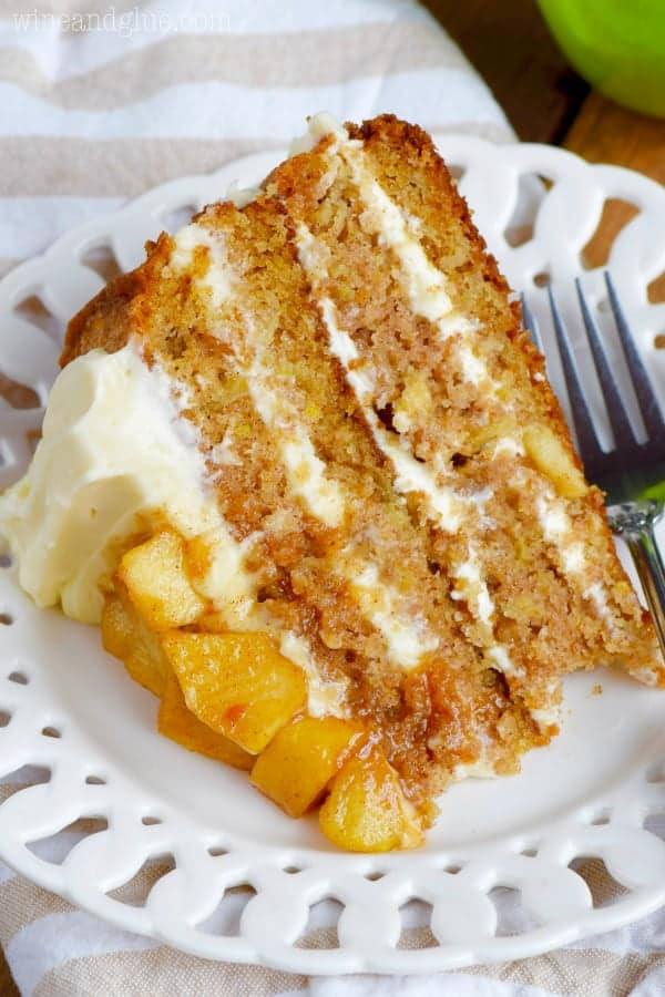 A slice of the Naked Apple Spice Cake is on a white plate showing the four distinct layers of the cake with fluffy frosting.