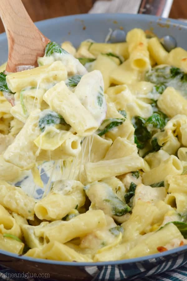 In a sauce pan, the One Pot Spinach Artichoke Pasta has a creamy and gooey texture from the cheese and sauce.