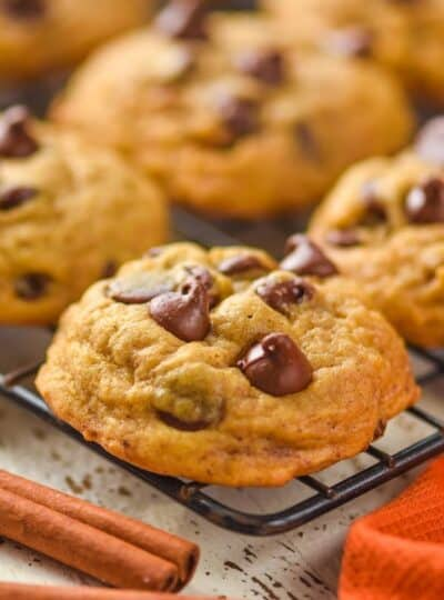 close up of a pumpkin chocolate chip cookie on a wire cooling rack