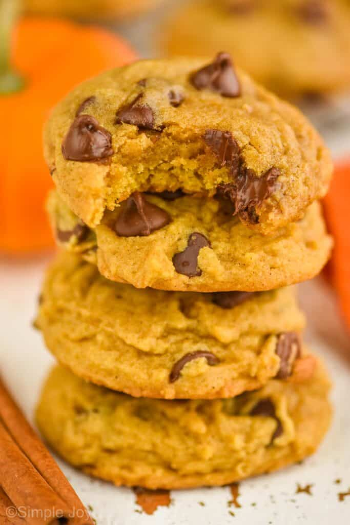 a small stack of pumpkin chocolate chip cookies with a bite missing on top