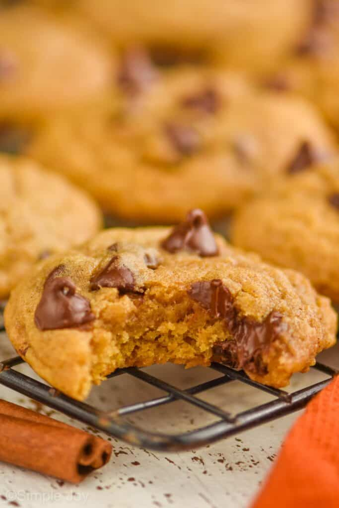 a pumpkin chocolate chip cookie on a cooling rack with a bite missing