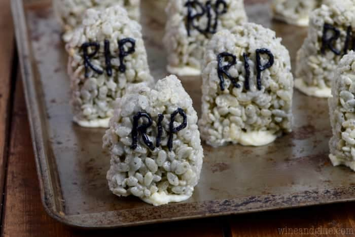 On a baking sheet, the Rice Krispies are in the shape of stone hedges in a grey color with the words RIP and stuck on the sheet pan by frosting.