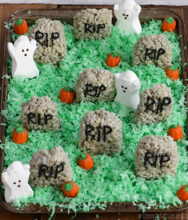 "Green coconut flakes are sprinkled everywhere like grass, and on top of the ""grass"" there are pumpkin candy corn, Rice Krispies Treat Hedge Stones, and ghost marshmallows."