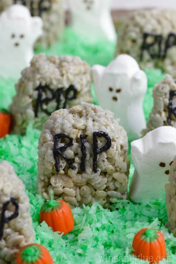 The Rice Krispies Treat Graveyard has a grey tint to it, shaped like a rounded top hedge stone, written on it with capital black letters RIP, and on top of green tinted coconut flakes.